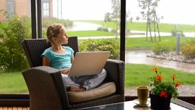 Little child girl sitting on the terrace in armchair with laptop stock video