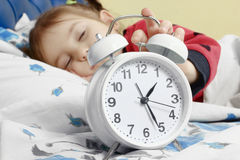 Little child girl sleeping in bed with alarm clock Stock Photo