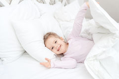 Little child girl in soft bed Stock Photo