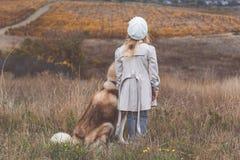 Little child girl is walking with husky dog Stock Photo