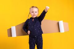 A little child girl is wearing homemade cardboard flying wings, pretending to be a pilot for a craft, imagination or Stock Photo
