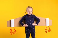 A little child girl is wearing homemade cardboard flying wings, pretending to be a pilot for a craft, imagination or Royalty Free Stock Photography