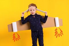 A little child girl is wearing homemade cardboard flying wings, pretending to be a pilot for a craft, imagination or Royalty Free Stock Images