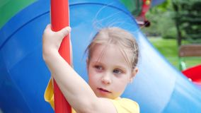 Little Child Girl on Playground. Little child girl in yellow t-shirt having fun on colorful playground on yard in park stock footage