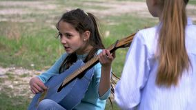 Child girls singer strum with acoustic guitar while her girlfriend standing listening music performer. Little child girls singer strum with acoustic guitar while stock video