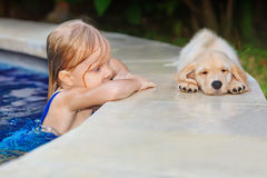 Little child with golden retriever puppy at poolside. Funny photo of little baby swimming in blue outdoor pool look at lazy retriever puppy. Children water royalty free stock image