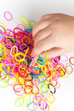 Little child hand and pile of small colorful rubber bands Stock Image