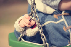 Little child hand on swing chains Stock Photos