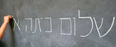 Little child hand writes Hello First Grade greetings in Hebrew. (Shalom Kita Alef) on a chalkboard in Israeli primary school at the beginning of the school year stock image