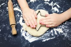 Little child hands with cookie cutter like a star making handmade traditional Christmas cookies. An overhead photo of kid`s hands,. Some flour, wheat dough Royalty Free Stock Image