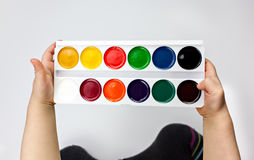 Little child hands holding watercolor palette royalty free stock image