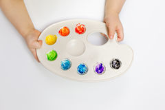Little child hands holding watercolor palette stock image