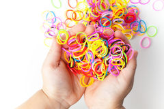 Little child hands and pile of colorful rubber bands Royalty Free Stock Photography