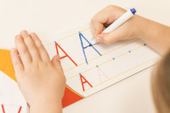Little child hands writing letter A. Learning to write. Little girl writing alphabet in a copy book at a desk. Learn Study Education School Knowledge Concept Royalty Free Stock Images