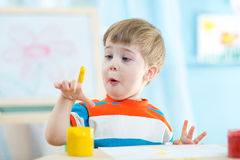 Little child is happy to paint picture while sitting at his desk Royalty Free Stock Photos