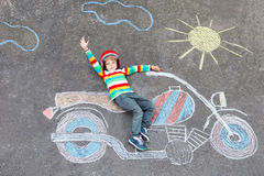 Little child in helmet with motorcycle picture Stock Photo