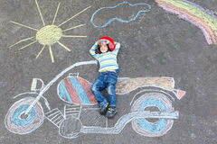 Little child in helmet with motorcycle picture drawing with colo Stock Images
