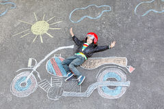 Little child in helmet with motorcycle picture drawing with colo Royalty Free Stock Image