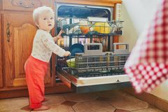 Little child helping to unload dishwasher. Baby girl standing on the floor in the kitchen and holding on to furniture. Little child at home royalty free stock images