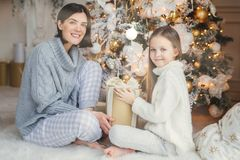 Little child and her mother sit on warm white carpet near decorated New Year tree, holds present in hands, have pleased and happy. Expressions, glad to spend royalty free stock photography