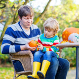 Little child and his father  making jack-o-lantern for halloween. Adorable little kid boy and his dad making jack-o-lantern for halloween in autumn garden Stock Image