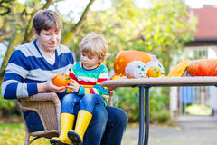 Little child and his father  making jack-o-lantern for halloween. Adorable little kid boy and his dad making jack-o-lantern for halloween in autumn garden Royalty Free Stock Photo