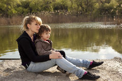 Little child with his mother looking away. Cute boy with woman sitting near a lake Stock Images