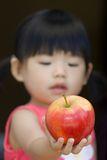 A little child hold an red apple Stock Photos