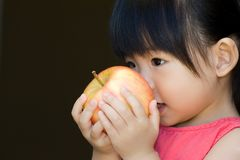 A little child hold a red apple Stock Photo