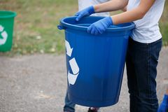 A little child holding in hands a blue recycling bin on a blurred natural background. Ecology pollution concept. A close-up picture of child`s hands holding a royalty free stock photography