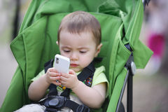 Little child holding mobile in the carriage Royalty Free Stock Photography