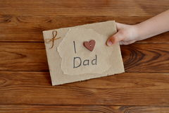 Little child holds a card I love dad. Postcard made of cardboard and wrapping paper, decorated with wooden heart, waxed cord. DIY Father's day or happy birthday royalty free stock photos