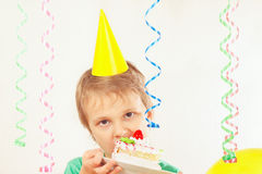 Little child in holiday hat tasting piece of birthday cake Royalty Free Stock Image