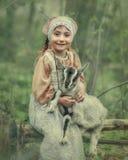A little child hugs a kid of goat