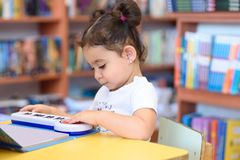 Happy child little girl reading a book. stock photos