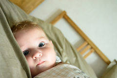 Little child with intent look. Little boy with intent look lying on the bed stock image