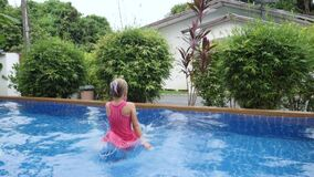 Little child jump and swim in swimming pool after coronavirus covid-19 epidemic