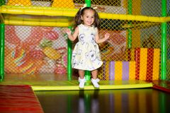 Little child jumping at trampoline in indoors playground. Active toddler girl having fun at sport centre. Stock Photo
