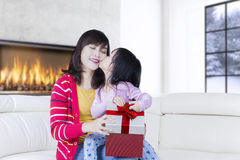 Little child kissing mother with gift. Portrait of little child kissing her mother cheek while holding a gift box at home Royalty Free Stock Photo