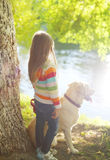 Little child with Labrador retriever dog dreams in summer Stock Photo