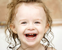 Little child laughing in the bath. Laughing little girl having fun in the bath stock photo