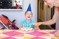 Little child laughing and woman lighting candles on birthday cak Royalty Free Stock Image
