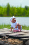 Little Child laughs loudly on the timber flooring. Little Child is sitting on the timber flooring near lake and laugh loudly. It is summer. Infant is one year Stock Image