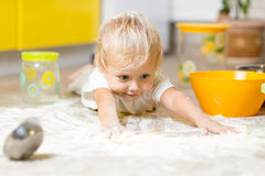 Little child laying on very messy kitchen floor. Little boy child laying on very messy kitchen floor. Toddler covered in white baking flour Royalty Free Stock Image