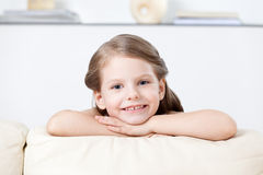 Little child leans to the white leather sofa Stock Photography
