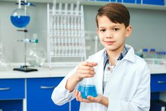 Little child with learning class in school laboratory holding test-tube. Little boy learning in school laboratory standing looking camera smiling holding test Royalty Free Stock Photography