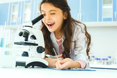 Little child with learning class in school laboratory looking in microscope
