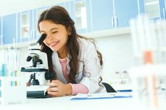 Little child with learning class in school laboratory using microscope stock photography