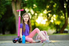Little child learning to ride a scooter in a city park on sunny summer day. Cute preschooler girl in safety helmet riding a roller Royalty Free Stock Photo