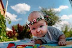 Little child lies on a blanket outside, summer, sunny day royalty free stock images